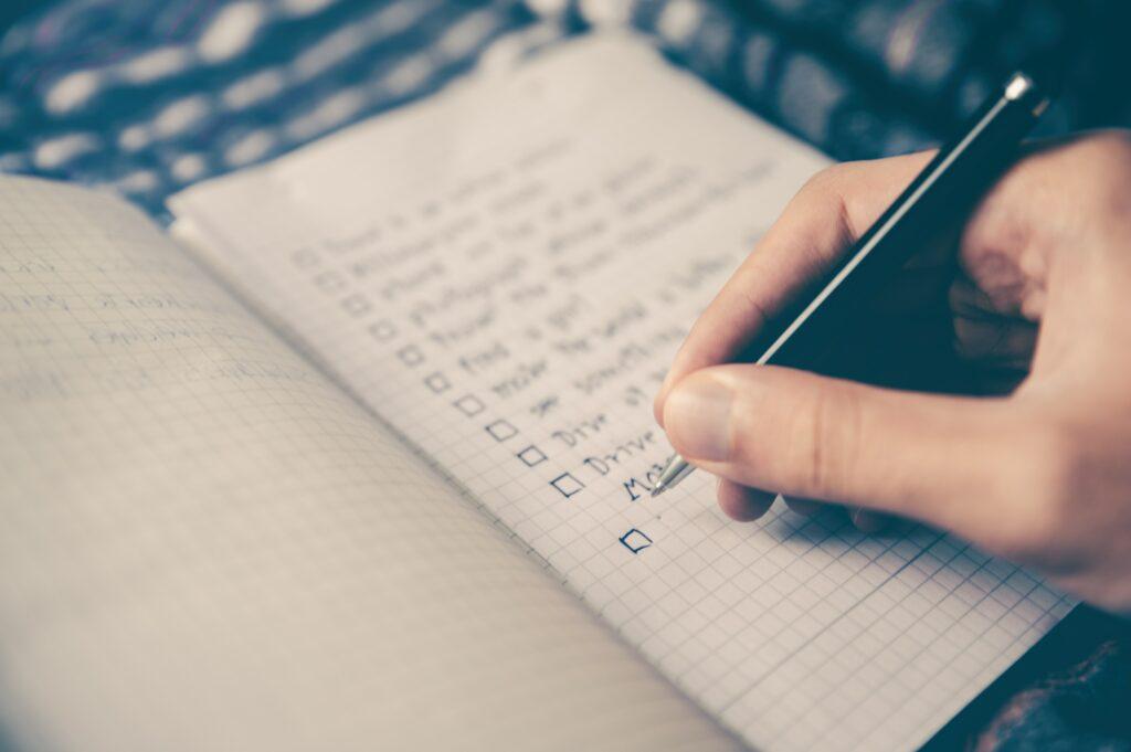 Une personne rédige une liste à cocher dans un cahier